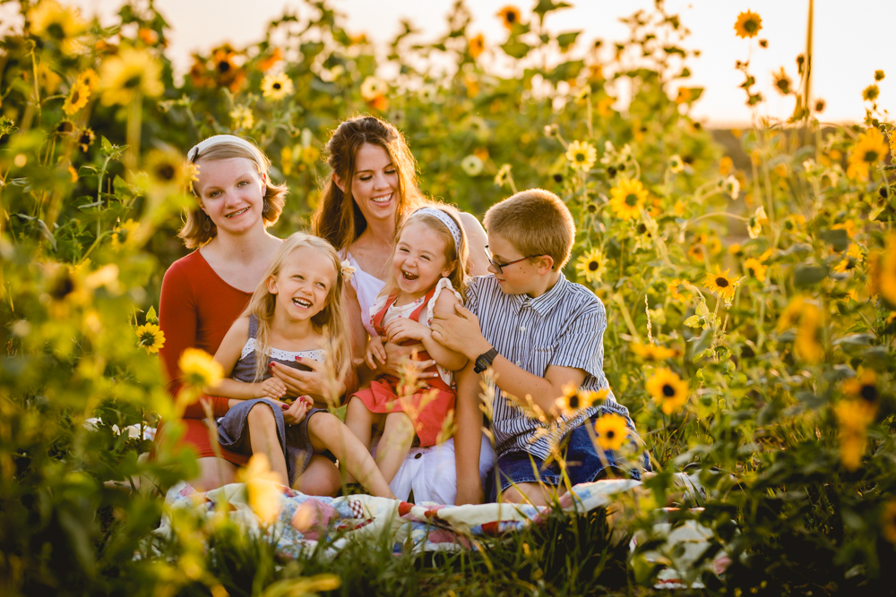 A family laughs and plays together in a sunflower field in a photo taken by Becky Michaud, Fort Collins photographer