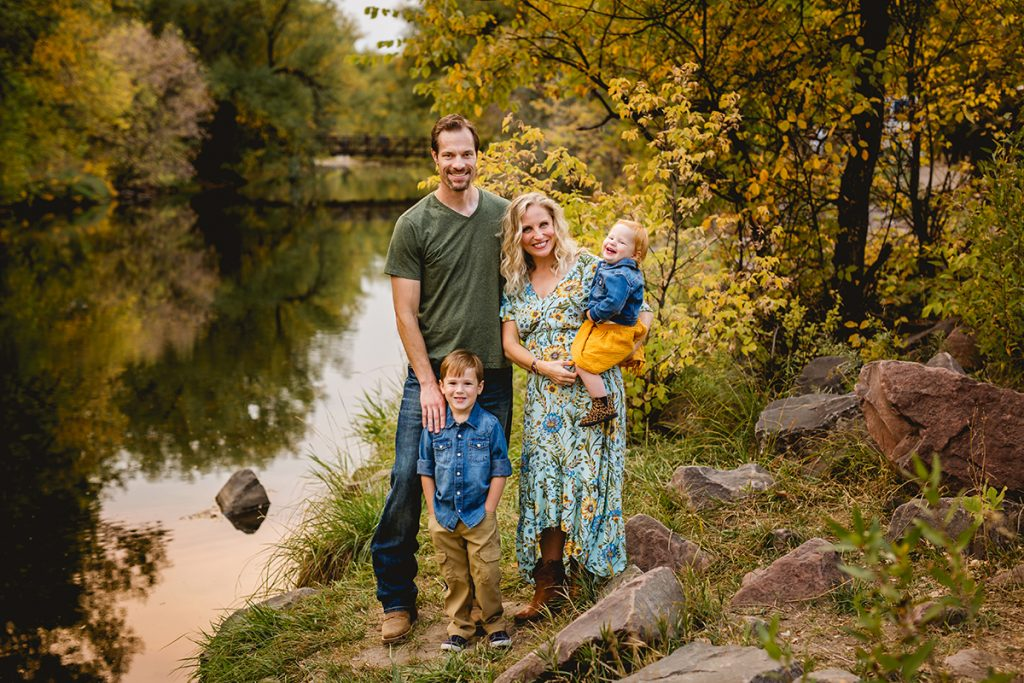 A family poses by the Poudre River in the fall