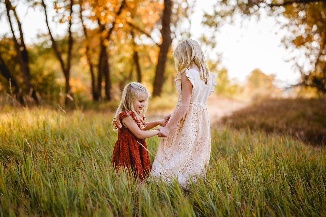 Two little girls in lace dresses play in a field together in Fort Collins