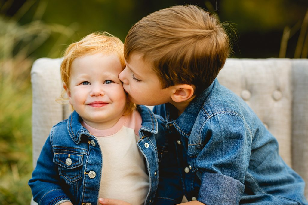 A boy kisses his sister on the cheek in a photo taken by Fort Collins photographer Becky Michaud