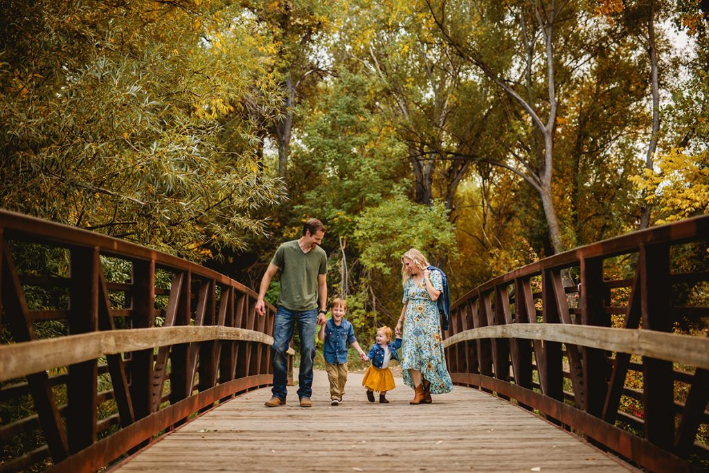Walking along a bridge together during a family photo shoot in north Fort Collins