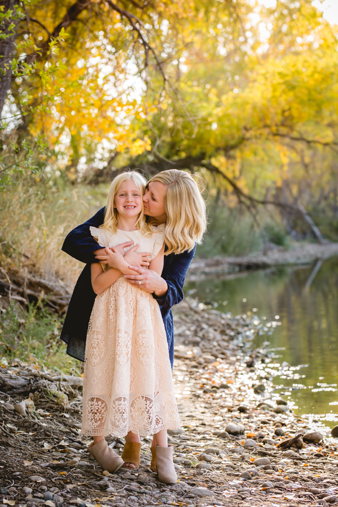 A mom kisses her daughter's cheek as they stand by a pond in Fort Collins, Colorado in the fall
