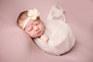 Photo of a baby on a pink blanket taken in her Fort Collins home during her newborn photo shoot