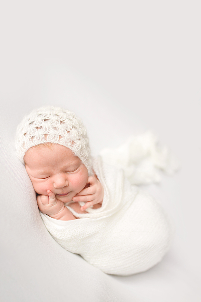 A baby girl wearing a white bonnet and white wrap poses for her newborn photo session in her home in Fort Collins, Colorado