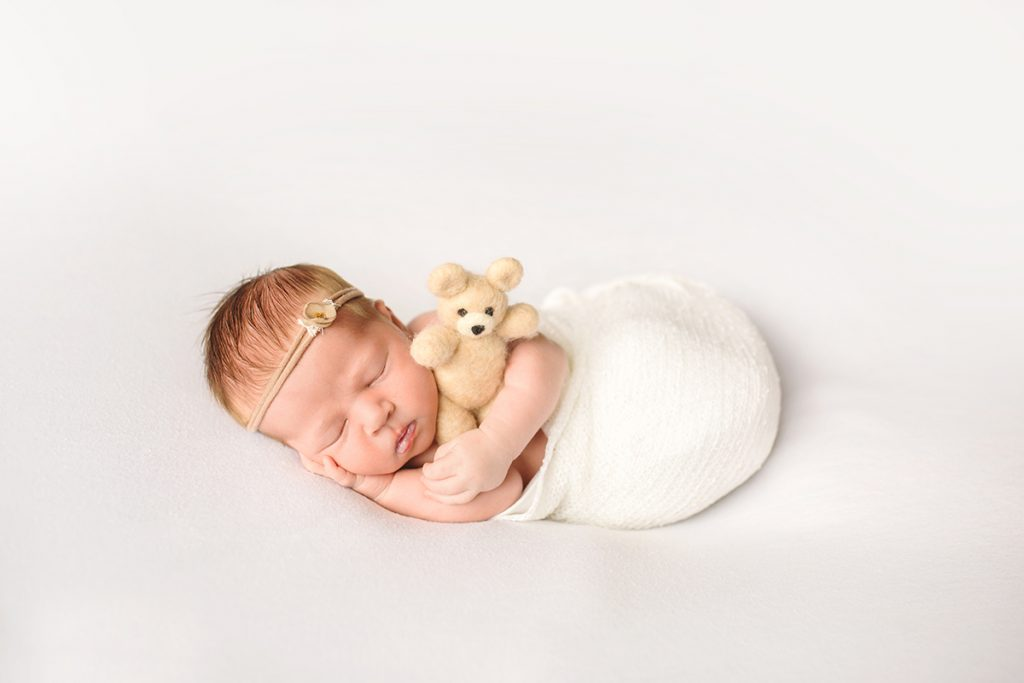Simple white newborn photo of a baby holding a teddy bear