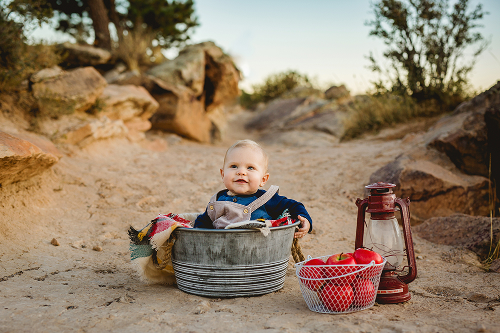 A baby sits in a metal tub with a basket of apples and red lantern in a mountain photo shoot in Colorado