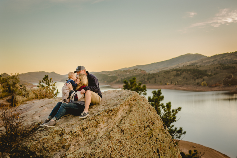 A family cuddles and plays together at Horsetooth Reservoir for their family photo session