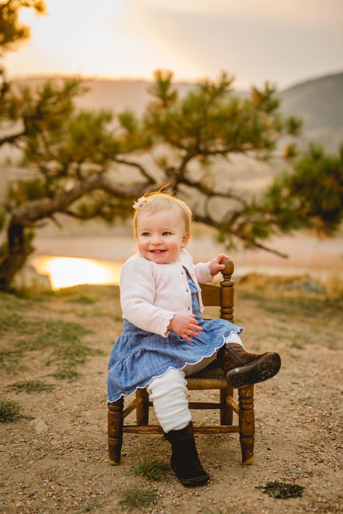 Baby girl sits in a wooden chair and smiles off camera during her Fort Collins photo session