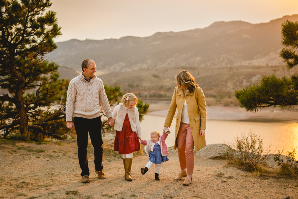 A family walks together as the sun sets over Horsetooth Reservoir behind them