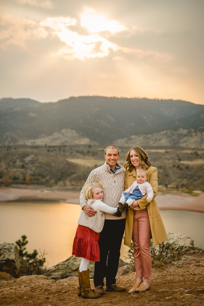 A family of four poses together at the top of Horsetooth Reservoir