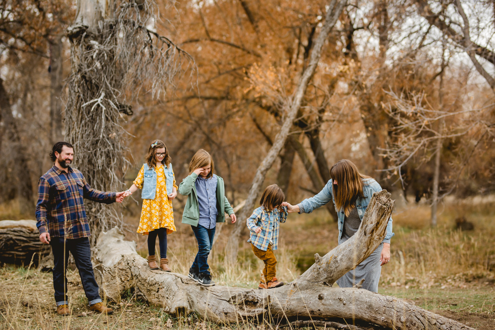 Parents help their kids walk along a log during their family photo session in Fort Collins