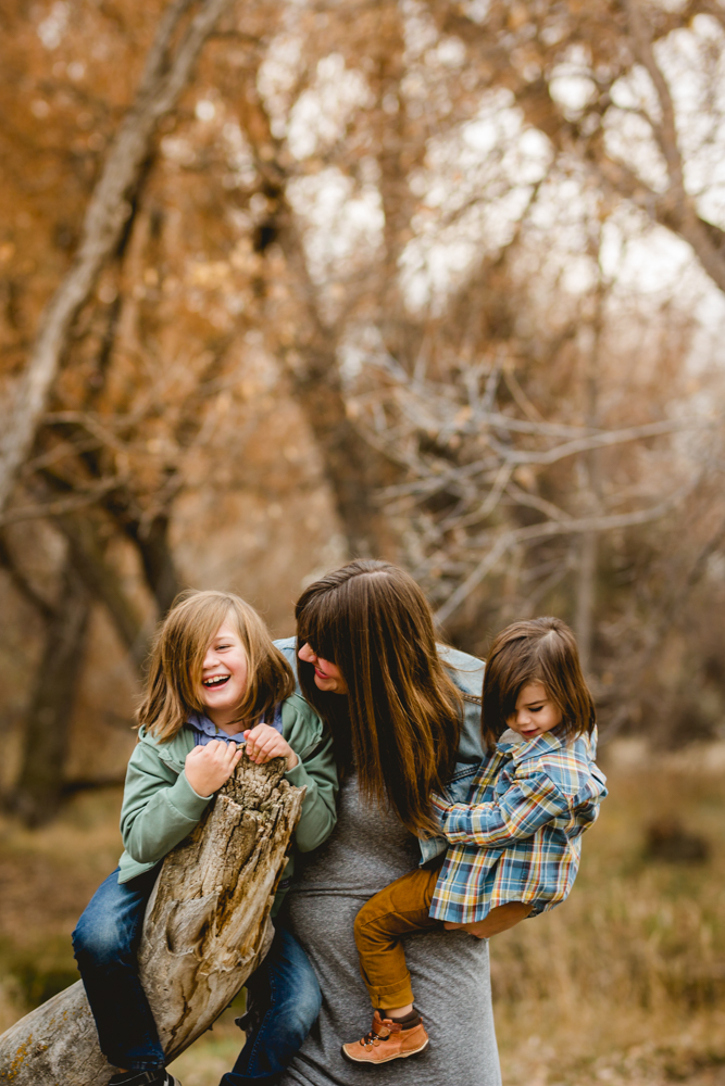 A mom plays with her boys in the forest in Northern Colorado