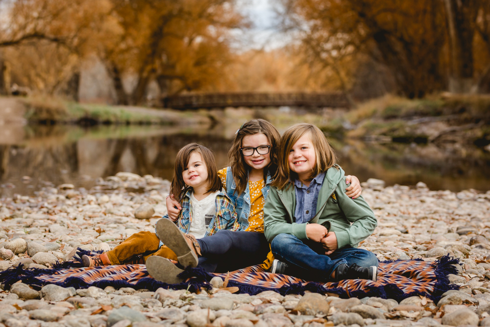 Three siblings sit by the river in fall in a photo taken by Becky Michaud, Fort Collins photographer