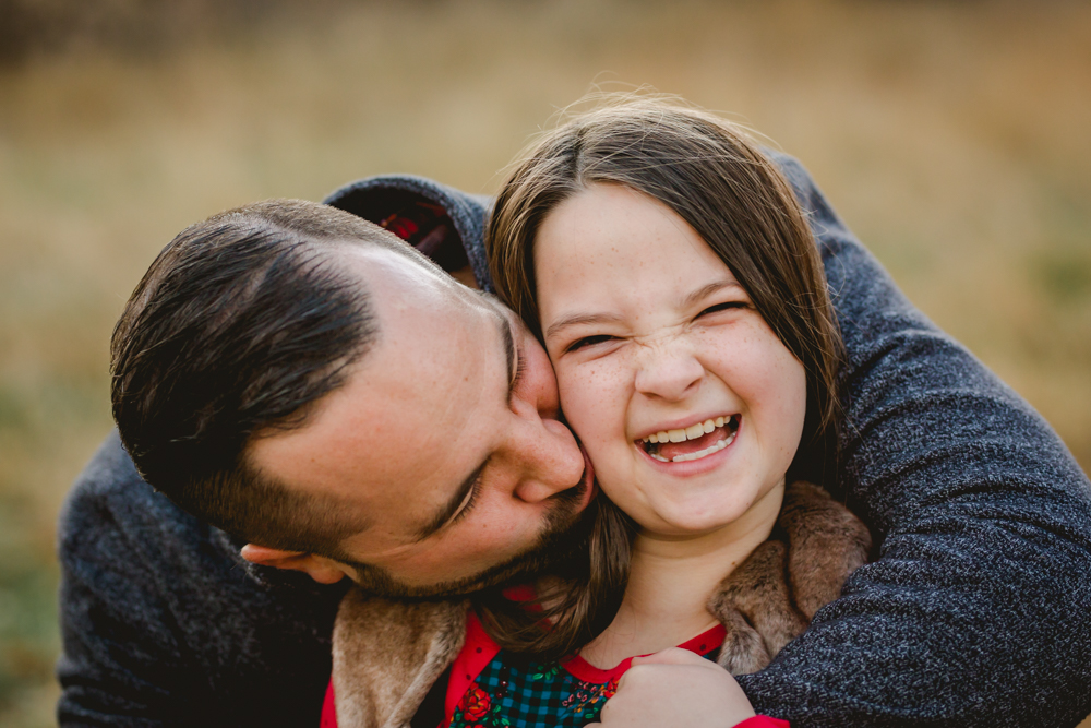 A dad kisses his laughing daughter's cheek