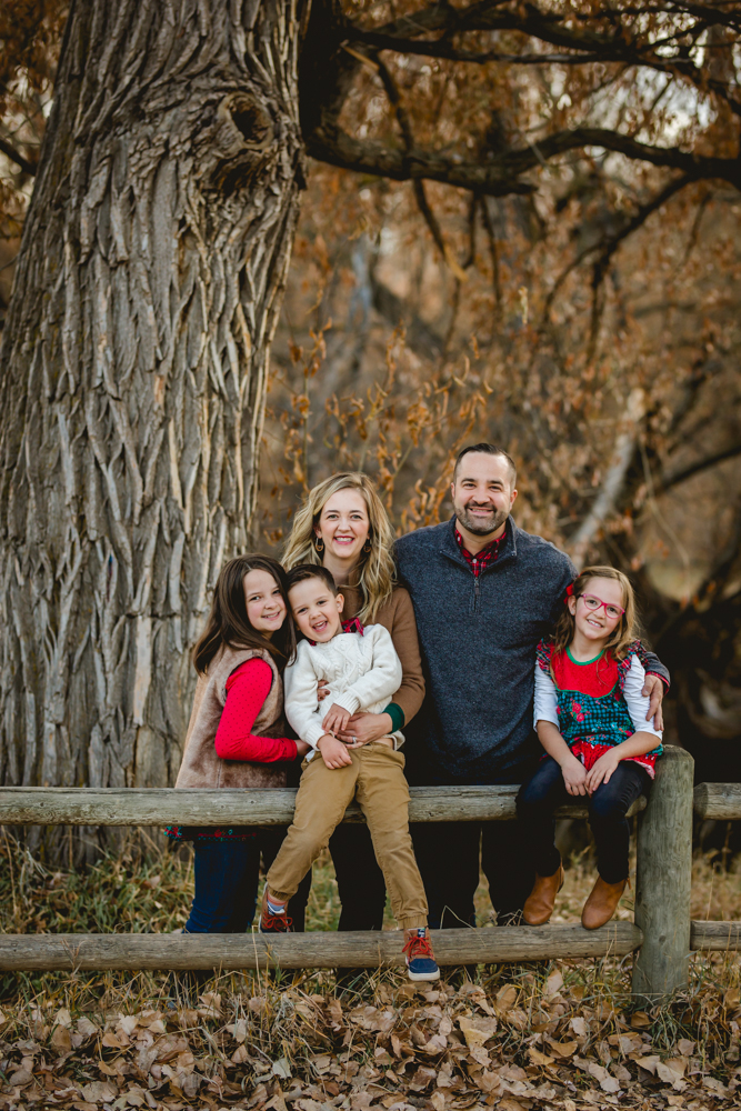 Family photo taken in a Fort Collins natural area of a family sitting on a fence