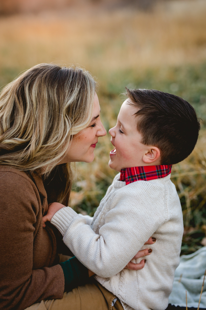 A mom plays with her little boy during their family photo session in Fort Collins