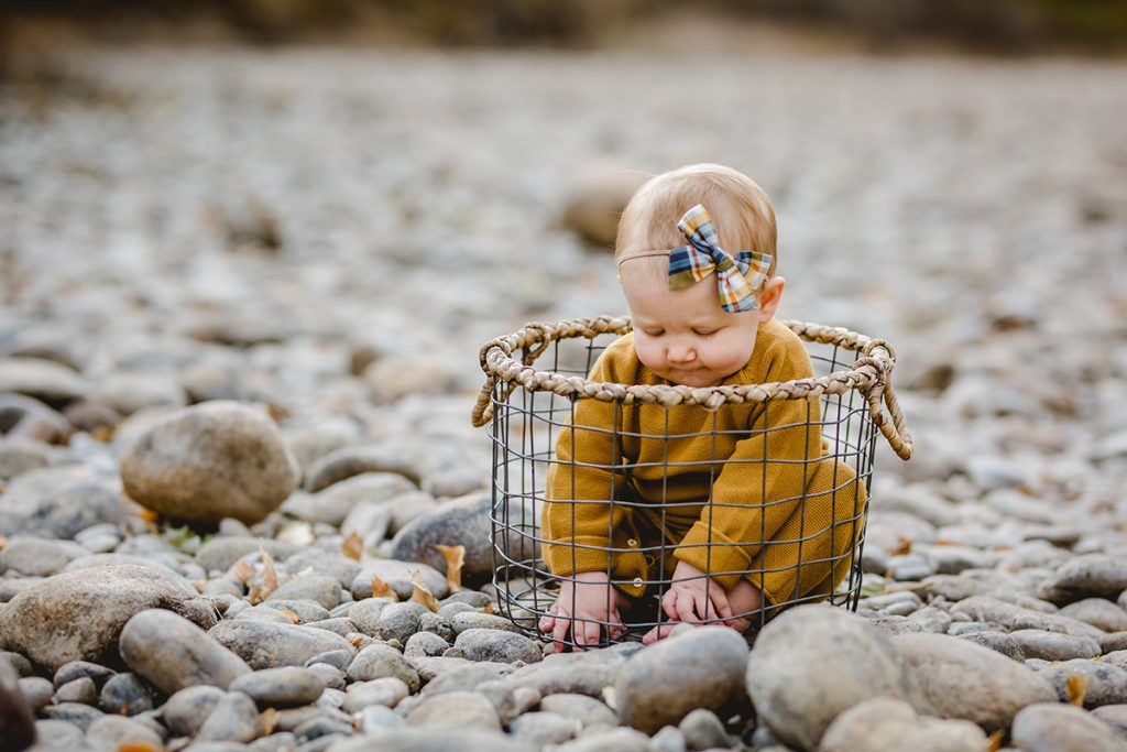 A baby plays in a basket on the river rock near the Poudre river during her family photo session