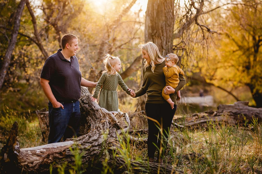 A family plays together in the forest for their family photography session Fort Collins, Colorado