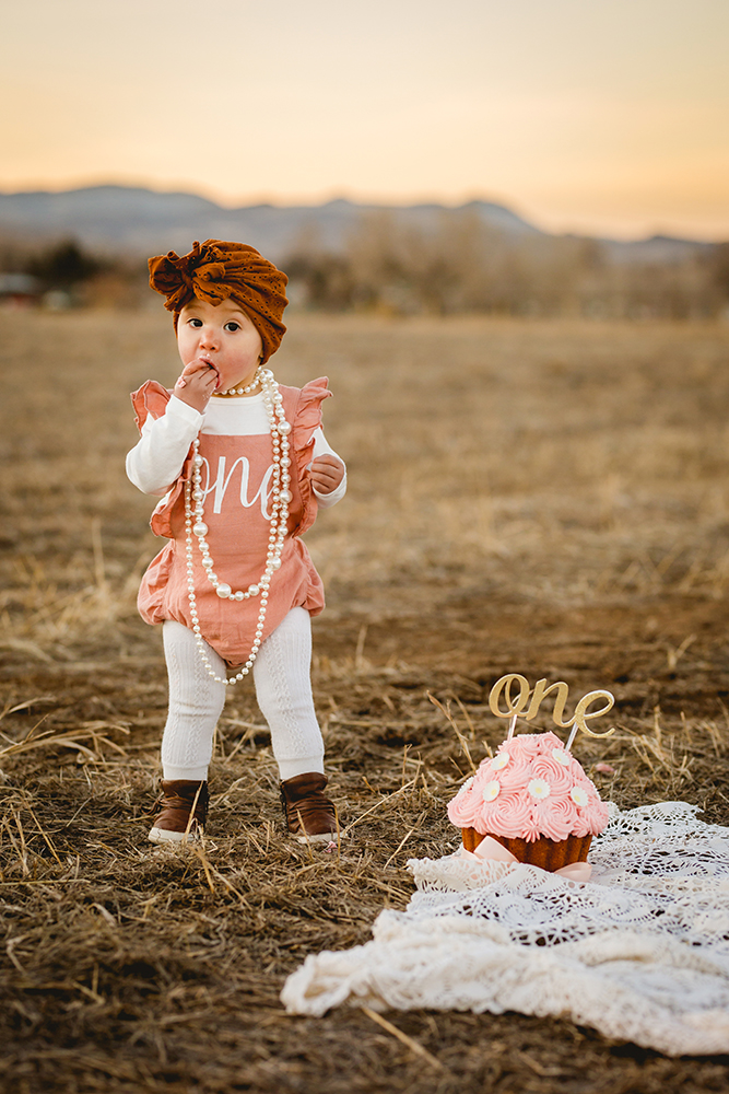 A baby girl eats a fistful of cake during her outdoor cake smash session in Fort Collins