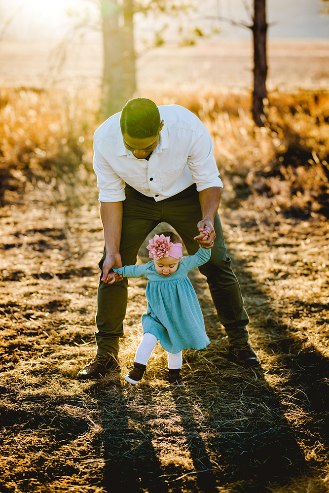 Baby girl walks with her dad during their family photo shoot at a Fort Collins park