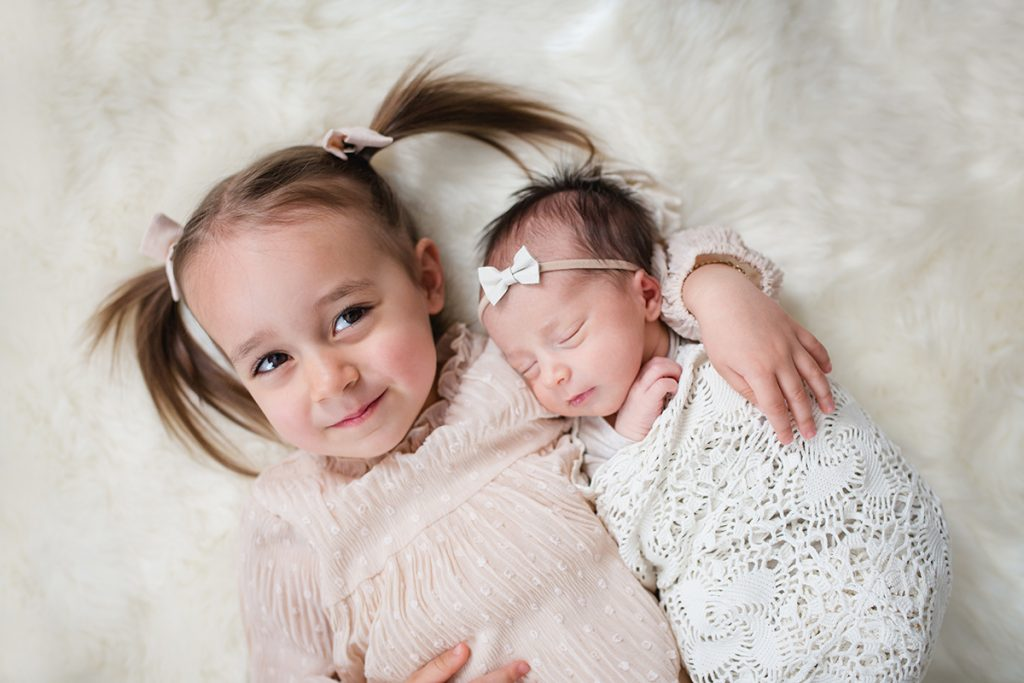 A big sister proudly poses with her baby sister during her newborn session in their Fort Collins home