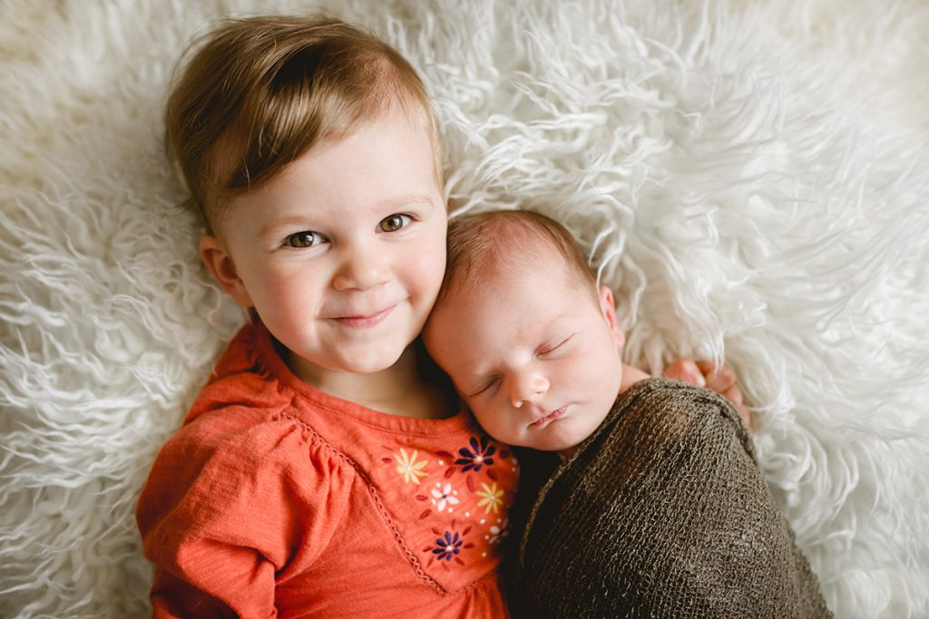 A toddler cuddles her new baby brother during his newborn photo session in their Loveland, Colorado home