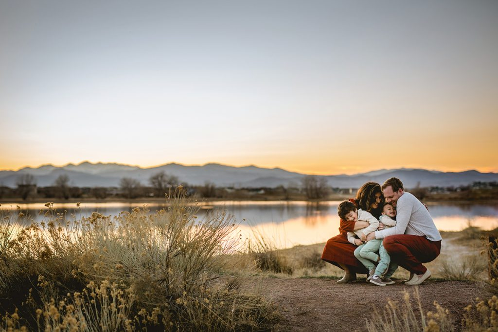 A family snuggles together with the Colorado mountains behind them