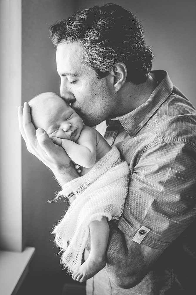 Black and white photo of a dad kissing his baby in a lifestyle newborn photography session in Northern Colorado