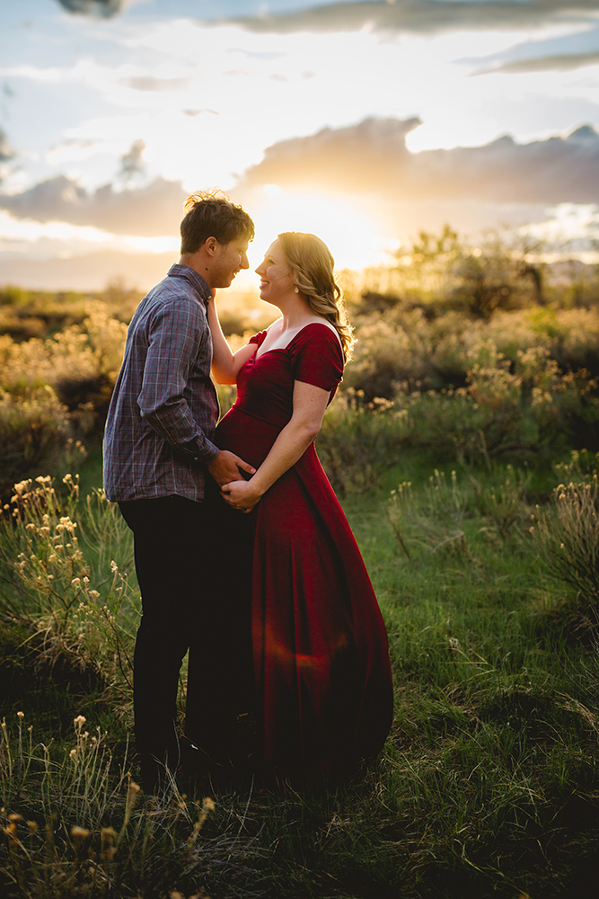 Pregnancy photo of a couple in golden light at a lake in Loveland, Colorado