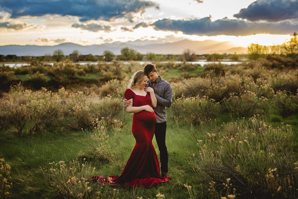 Maternity photography featuring a couple at sunset with mom wearing the Chicaboo Athena gown in Northern Colorado