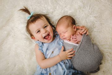 A little girl smiles as she holds her brother during his newborn photo session in their Fort Collins home