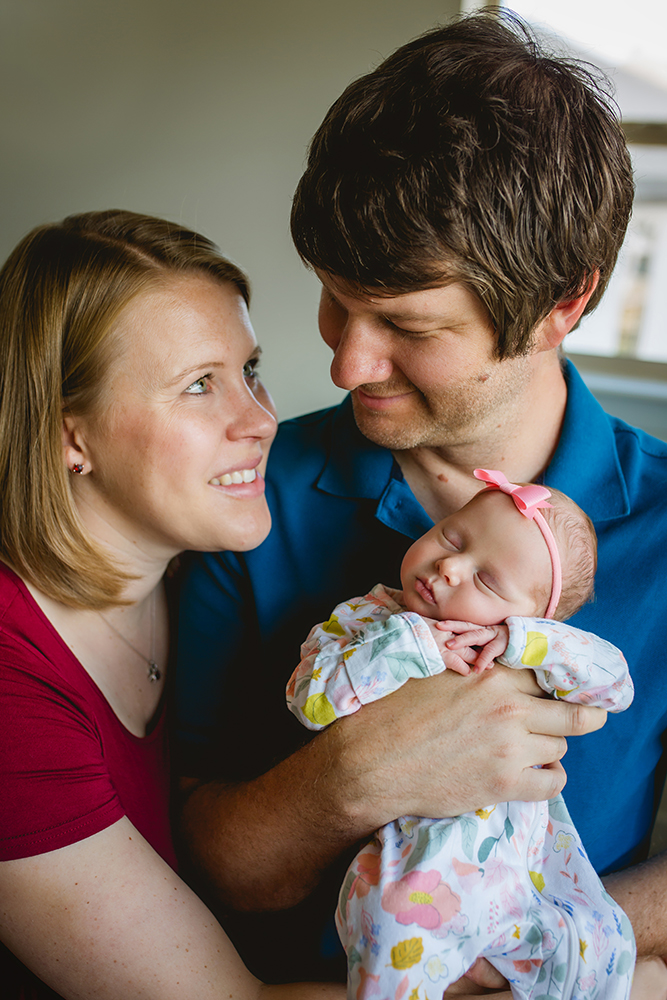 Lifestyle newborn photo of a couple with their new baby girl in their Fort Collins home