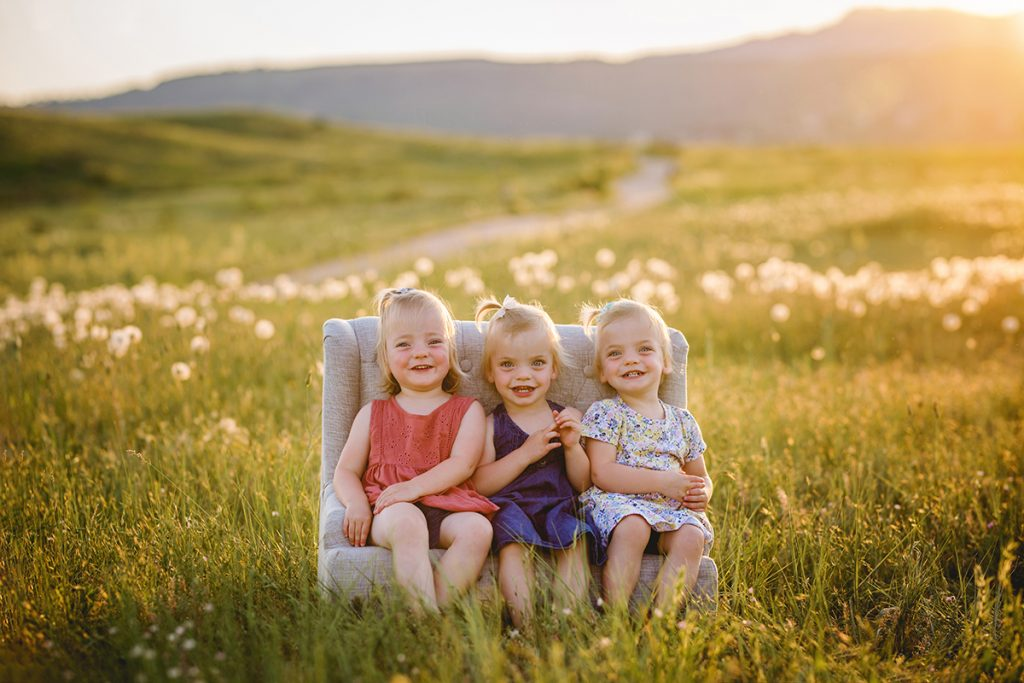 Three little girls sit on a couch in a field in a photo taken by Becky Michaud, Fort Collins photographer