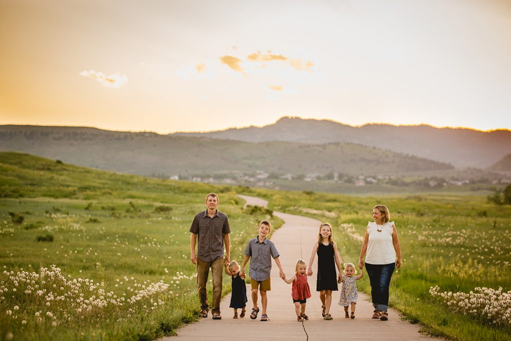 A family walks down a path together holding hands with the Colorado foothills in the background