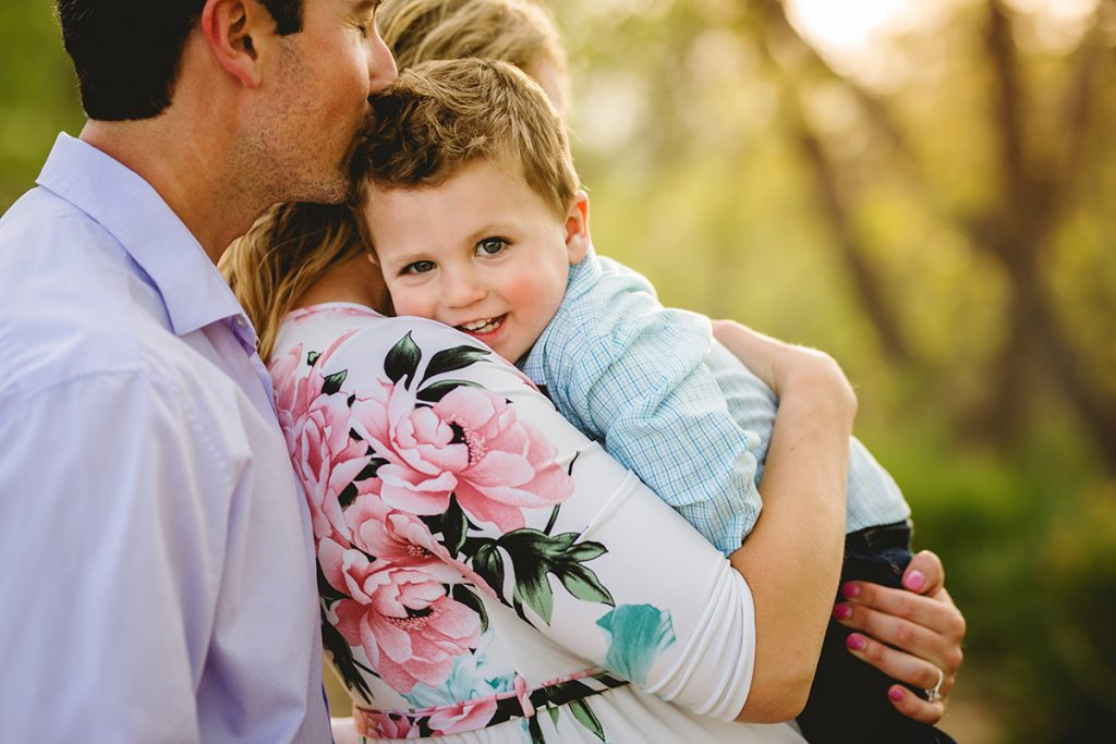 A little boy snuggles with his mom as his dad kisses him on the head during their family photo session in Fort Collins