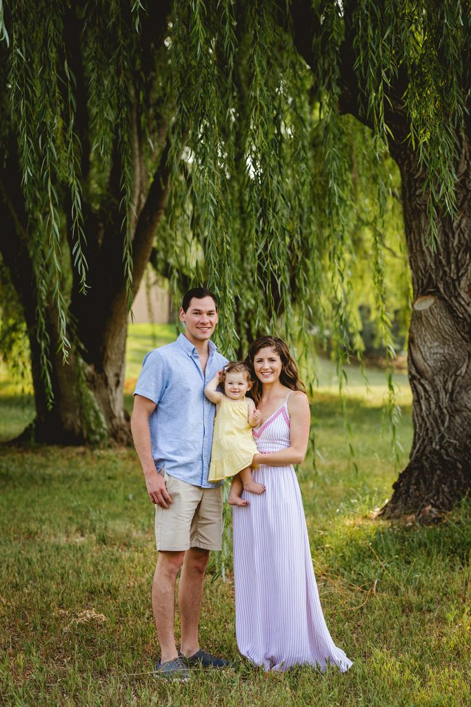 Family of three poses by the willow trees in Northern Colorado