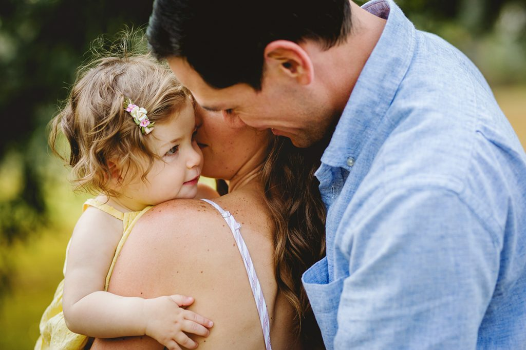 A dad looks at his baby girl during their family photography session in Fort Collins