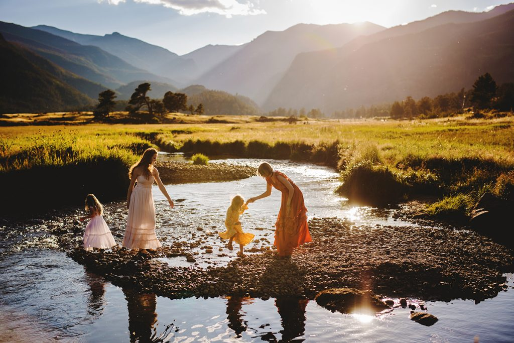 A family plays in the creek during their photography session at Rocky Mountain National Park