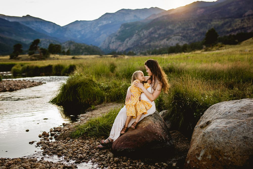 A mother snuggles her daughter as they pose for a photo in Rocky Mountain National Park