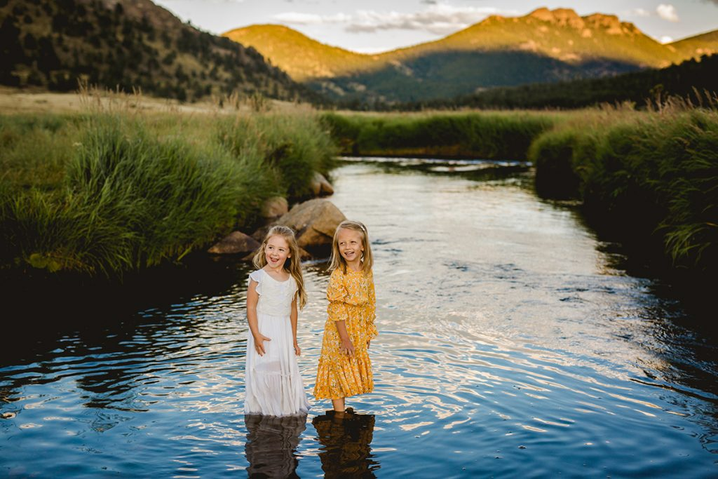 Two little girls play in the river in Rocky Mountain National Park in a photo taken by Becky Michaud, Colorado Photographer