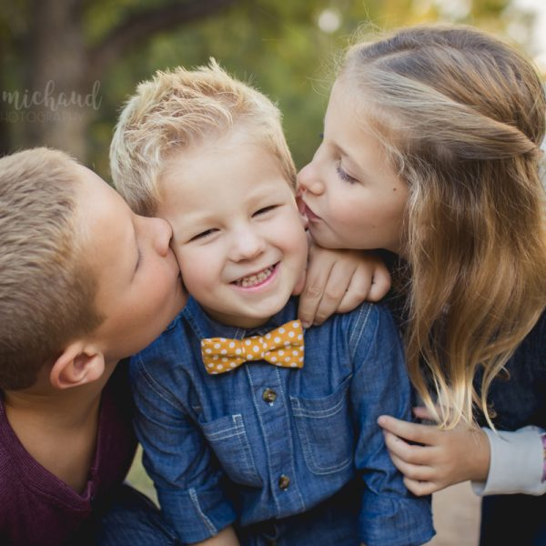 Big brother and sister kiss little brother on the cheeks during their family photos with Becky Michaud, Fort Collins photographer
