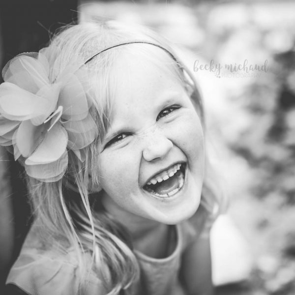 black and white portrait of a girl laughing taken by Becky Michaud, child photographer in Colorado
