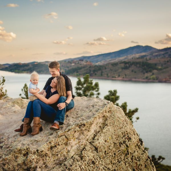 Photo of a family of three on a beautiful cliff overlooking Horsetooth Reservoir